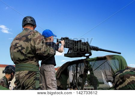 LAUDUN, FRANCE - MAY 01 2014: Little boy with machine gun during a military show in Laudun France