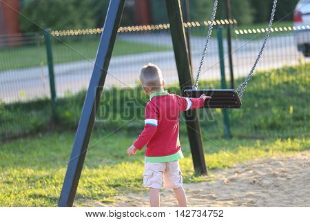 a little blond boy pushing empty swing at a playground outdoors
