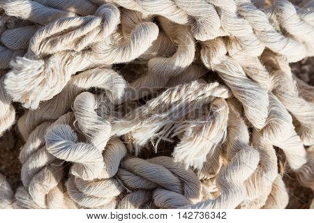 A pile of old damaged tangled rope abandoned on the ground