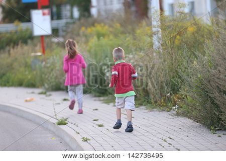 little boy following his sister running outside on a sidewalk