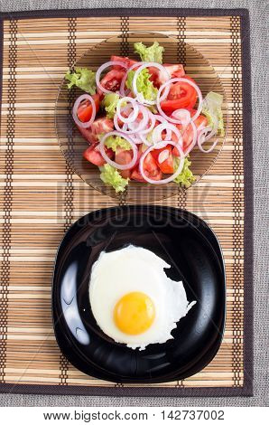 Fried Egg With Yolk On A Black Plate And A Salad Of Tomato