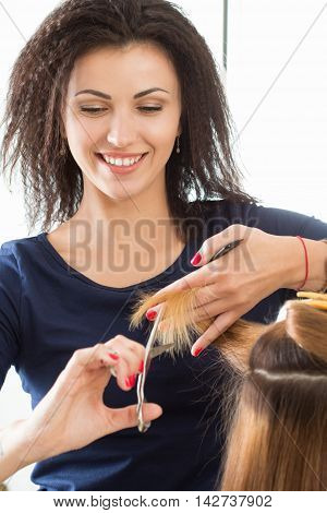 Smiling female hairdresser cutting client hair tips. Keratin restoration healthy hair latest hair fashion trends changing haircut style shorten split ends instrument store concept