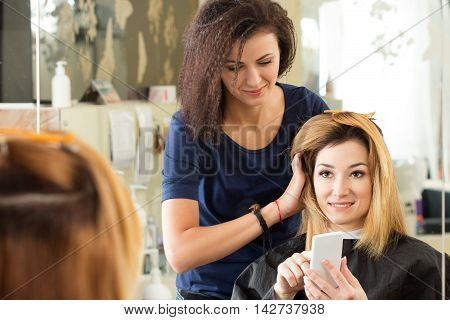 Smiling client showing her hairdresser on mobile phone what haircut she wants to do. Healthy hair latest hair fashion trends changing haircut style concept