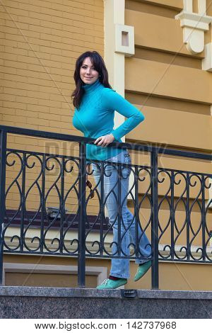 Beautiful girl in a blue turtleneck near the railing. People