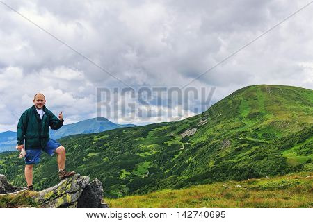 Portrait of young men tourist who standing on a rock and showing thumbs up Carpathian mountains summertime journey