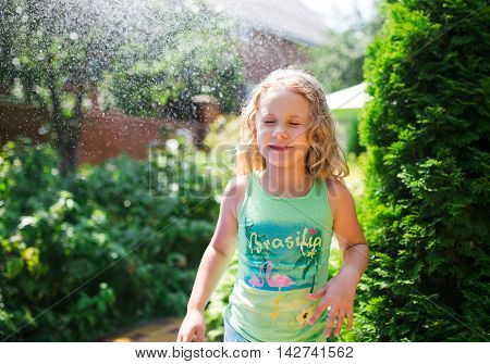 Preschooler cute girl playing with garden sprinkler. Summer outdoor water fun in the backyard