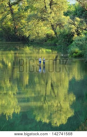 OVCAR BANJA, SERBIA - AUGUST 05, 2016: boy fishing under the watchful eye of his father in Morava River that flows in the lush green of Ovcar Gorge