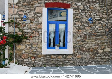 Greek style blue and white window on stone wall blue laterns and flowers
