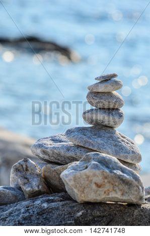 Marble zen stones on a rock against blue sea bokeh