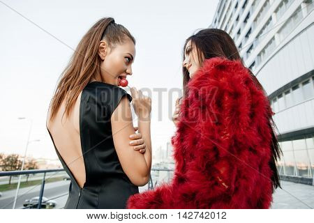 Two Young Fashion Girls Sucking Lollipops