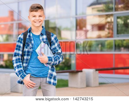 Happy teen boy holding books on the first school day. Outdoor portrait. Young student beginning of class after vacation. Back to school concept.