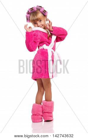 Full length portrait of a little girl in pink bathrobe with curlers on her head isolated on white background. Happy child showing Ok gesture.