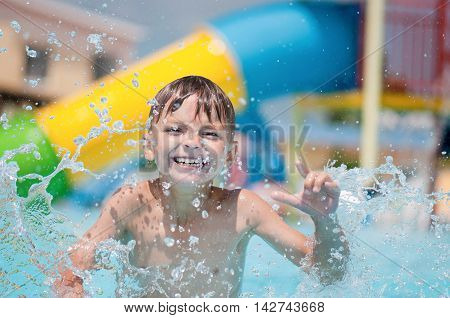 Happy boy, relaxing on a swimming pool at aqua park