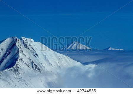 Kamchatka mountain tops in clouds. Aerial view