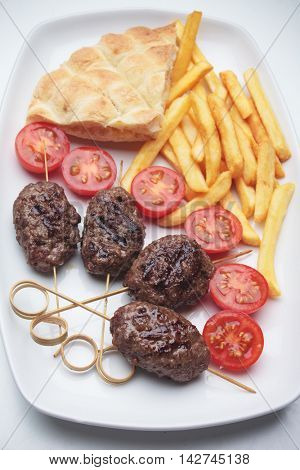 Kofta kebab, oriental minced meat kebab with pita bread and french fries