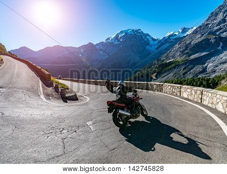 Beautiful sunset above the motorbike on the famous road in mountains Alps Passo Stelvio