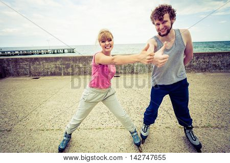 Outdoors activities sport and hobby. Exercises for healthy and strong body.. Friends stretch together have fun riding rollerblades showing thumbs up.