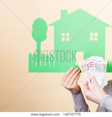 Home real estate credit mortgage concept. House cutout and cash. Hands hold banknotes and house.