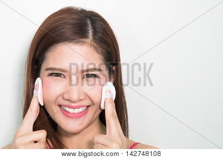 Attractive Asian Woman Using Puff To Apply Powder