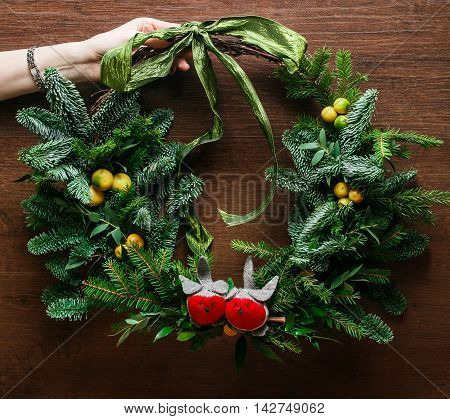 Christmas floral wreath decoration with baubles, red bow, holly and winter greenery over oak background
