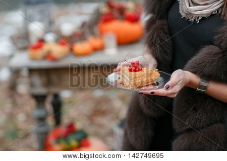 halloween inspiration. cake in hands. Autumn still life. pumpkin, dry roses, viburnum honey cake. Honey in a vase. dry twigs. on the table