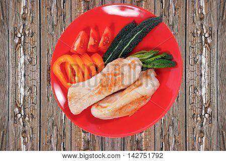 fresh roast turkey meat fillet steak served with vegetables on plate over wooden table