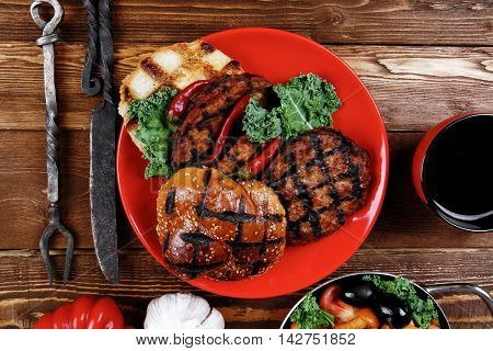fresh grilled beef hamburger served on red plate with black coffee glass chili pepper olives green kale leaves mushroom bell garlic and forged vintage antique cutlery over wooden table