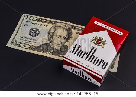 Indianapolis - Circa August 2016: Marlboro Cigarettes and Twenty Dollar Bills Representing the High Costs of Smoking. Marlboro is a product of the Altria Group VIII