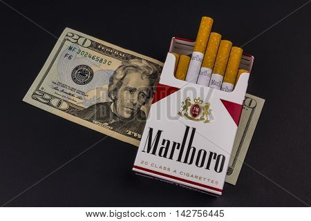 Indianapolis - Circa August 2016: Marlboro Cigarettes and Twenty Dollar Bills Representing the High Costs of Smoking. Marlboro is a product of the Altria Group XI