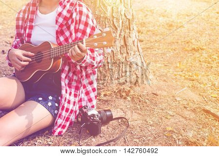 Beautiful asian women playing ukulele guitar at outdoor in pastel or vintage style color. copy space background