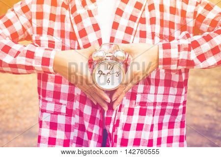Young woman with alarm clock in a hand concept. pastel or vintage style color