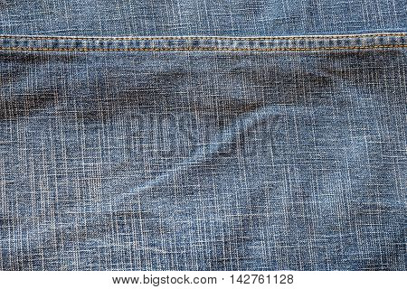 Texture of fabric blue jeans textile with seam. Close up detail background