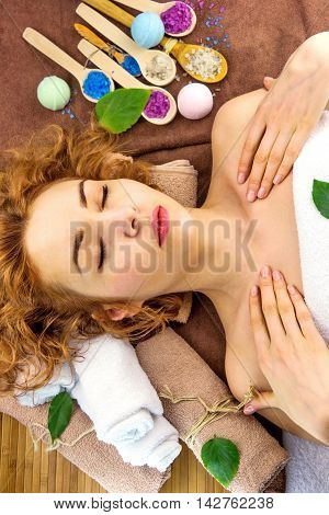Pretty young woman with curly hair relaxing with spa products
