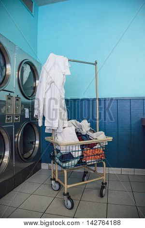 Washing clothes and drying at the Laundromat with chrome washer and dryer units along the isle and walls.