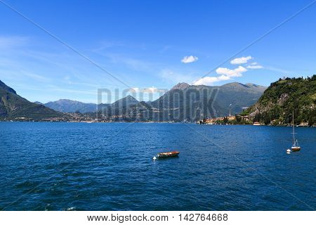 View Towards Lake Como With Boats And Village Varenna With Mountains In Lombardy, Italy