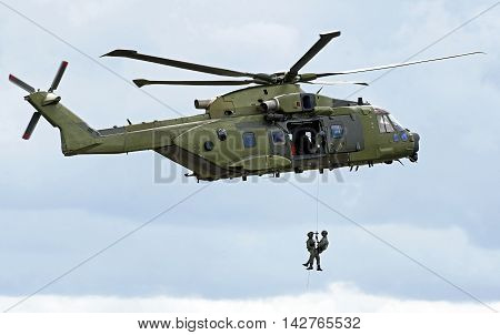 Military rescue helicopter hoisting personnel with clouds in the background
