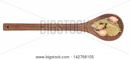 Garlic in a wooden spoon with bay leaf herb and black peppercorns isolated over white background.