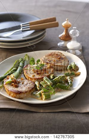 Fried veal with asparagus granada on white plate