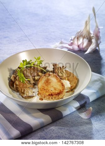 Veal Granada with garlic cream on white bowl and tablecloth