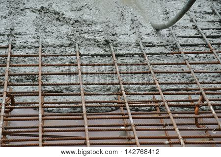 SELANGOR, MALAYSIA -JUNE 20, 2016: The wet concrete is poured on a steel reinforcement to form strong floor slabs.