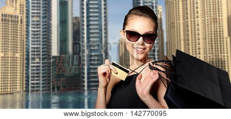 sale, finances, fashion, people and luxury concept - happy beautiful young woman in black sunglasses with credit card and shopping bags over dubai city street background