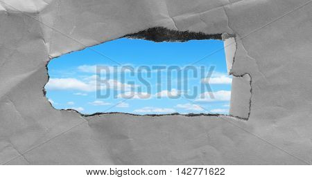 Hole in the sheet of paper and sky inside