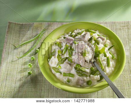 Veal Risotto Primavera or porridge in green bowl