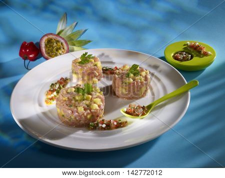 Pineapple passion veal tartare on white plate in restaurant