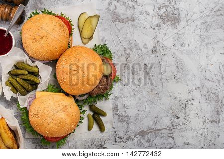Hamburgers grilled and cheeseburger on wooden round board on light rough surface with copy space top view