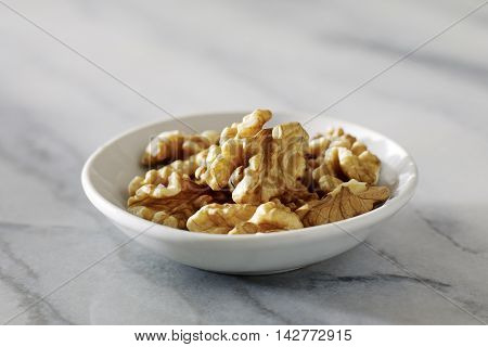 Dried walnuts in white plate on Marble Surface