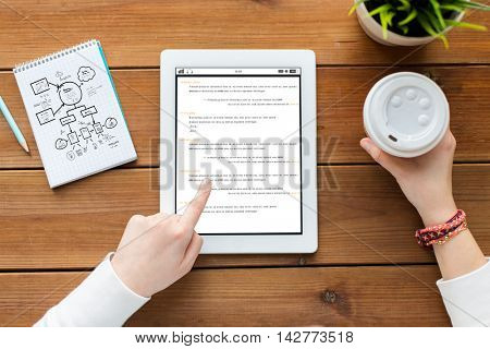 programming, business, education, technology and people concept - close up of woman with coding on tablet pc computer screen and coffee on wooden table