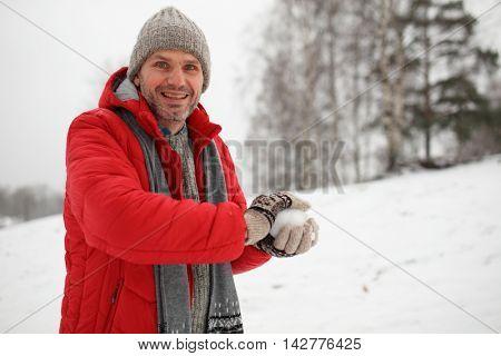 Mature man making snowball during snowball fight