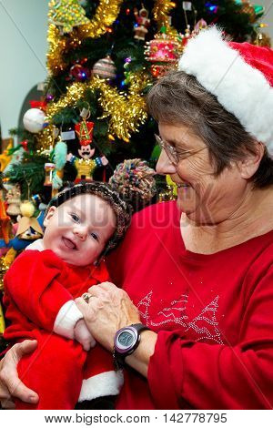 A grandmother in a Santa hat holds her grandson on his first Christmas. He is smiling for the camera and she is looking at him. They are standing in front of the Christmas tree.