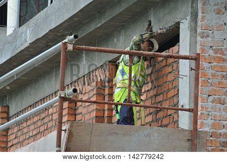 JOHOR, MALAYSIA -JUNE 28, 2016: Bricklayer lay clay bricks to form building walls at the construction site.